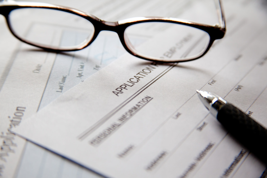 Application form with glasses and pen
