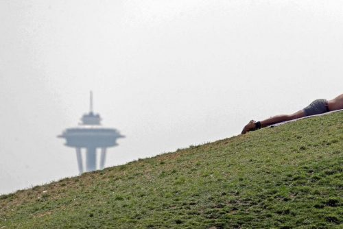 A man sunbathes in view of the Space Needle obscured by smoke.