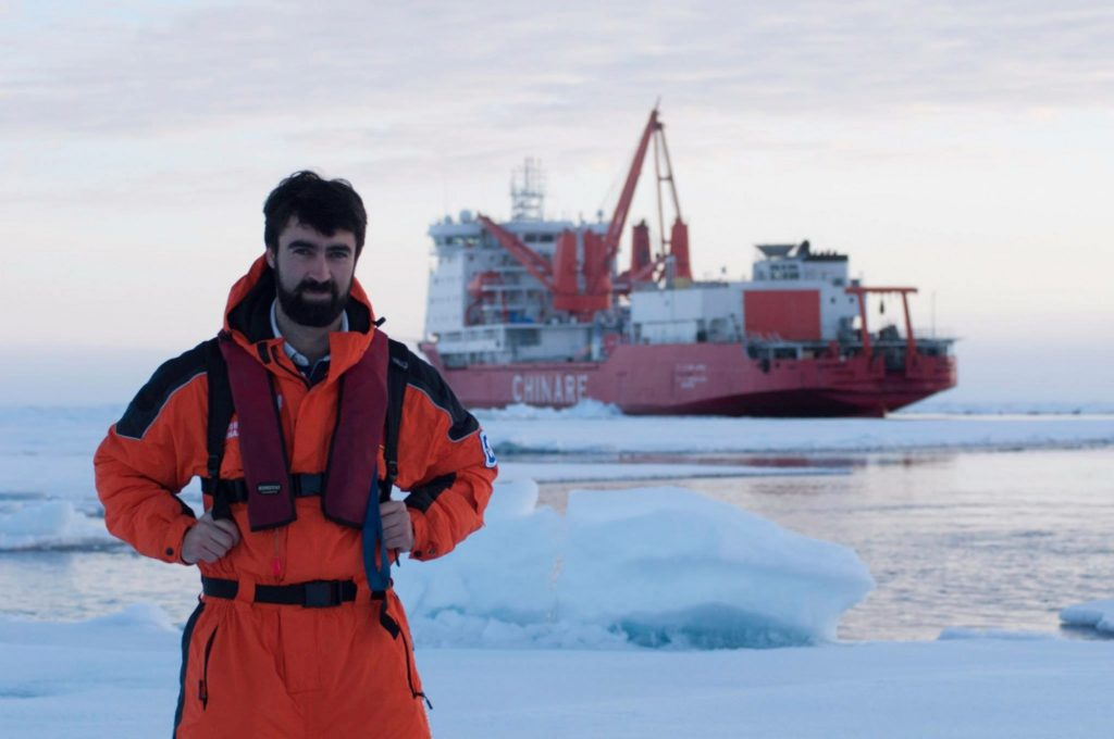 Andrew standing on ice in front of research ship