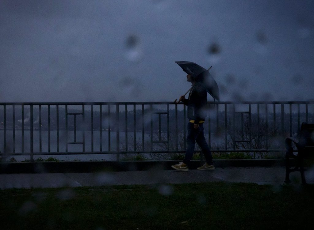 person walking in the rain on a dark day in Seattle
